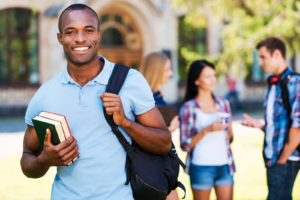 Handsome young African man holding book and smiling while standing against university with his friends chatting in the background ** Note: Soft Focus at 100%, best at smaller sizes